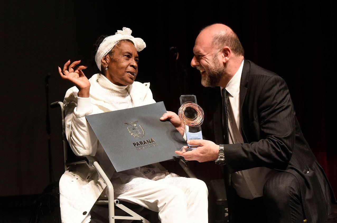 Vó Neli de Oxalá recebeu o troféu das mãos do secretário da Cultura, João Luiz Fiani.